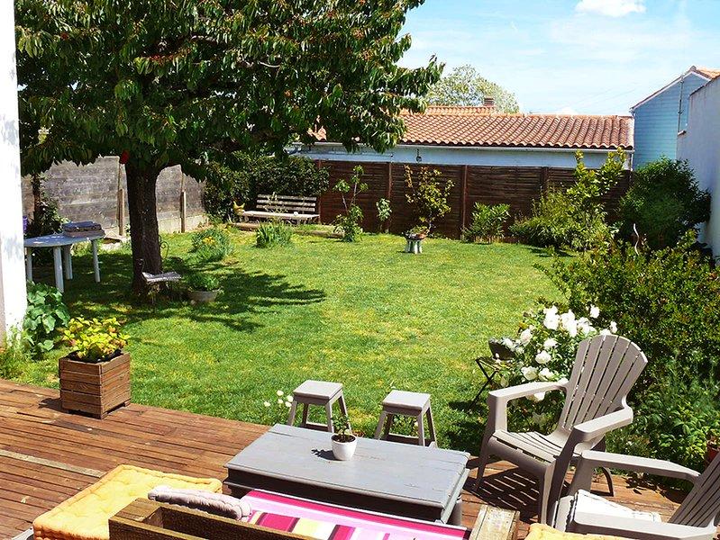 Vue vers le cerisier, ideal pour les repas du midi a l'ombre. Tres grande table de jardin 10 personn