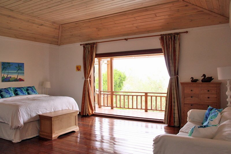 Master bedroom with the double doors open to the balcony and garden.