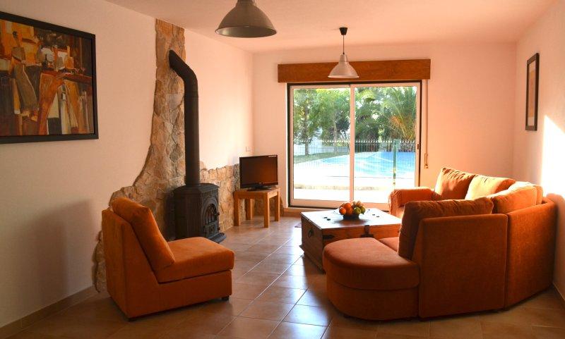 sala de estar com vista para o terraço, piscina e, eventualmente, pôr do sol.