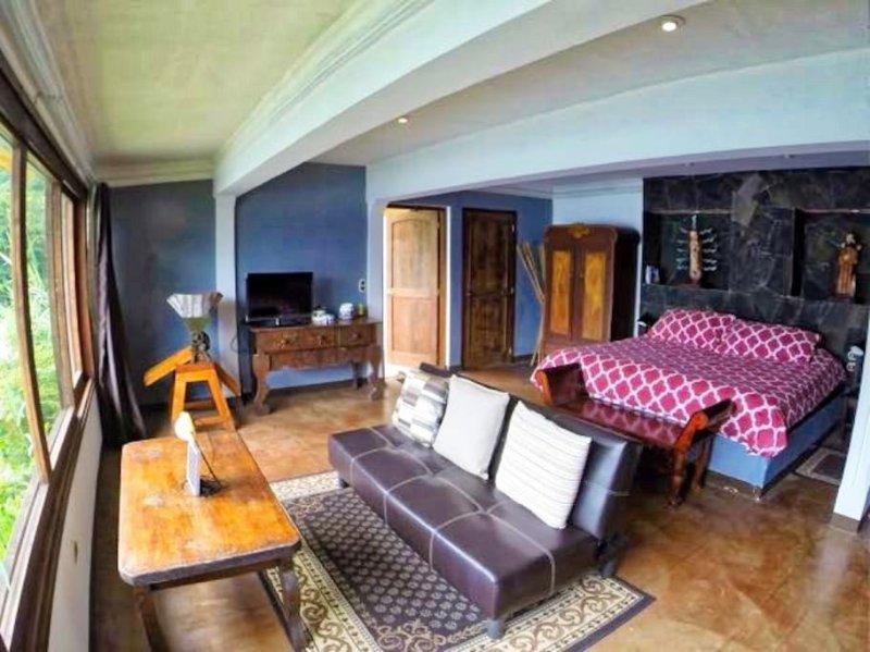 Amplio piso abierto con vistas desde el sofá y una cama matrimonial. Aseo cerca de la entrada del baño separared