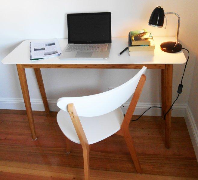 Mantenerse en contacto y ponerse al día en los correos electrónicos de última hora o de trabajo en el escritorio de ordenador privado en el dormitorio grande.