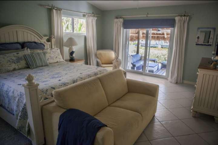 Coastal geïnspireerd master bedroom suite, compleet met een kingsize bed en een eigen toegang tot de patio.