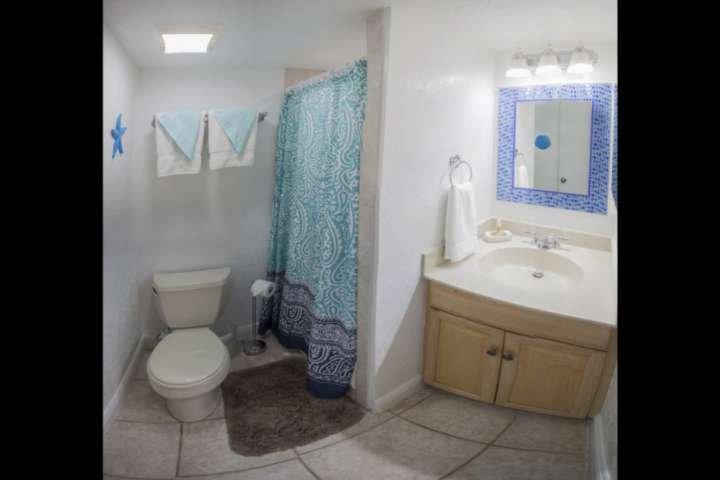 En banheiro de hóspedes suite com um stand up chuveiro e lavatório único.