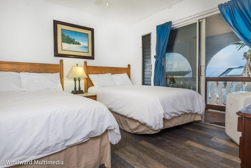 Prima camera da letto con 2 letti matrimoniali, unità AC portatile, ventilatore a soffitto e accesso al lanai