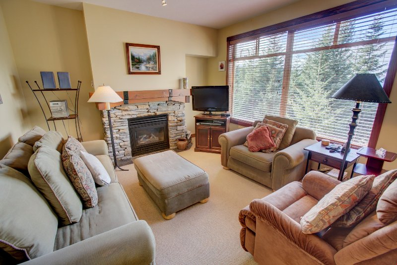 Relax in front of the fireplace in the spacious living room. Photos are representative.