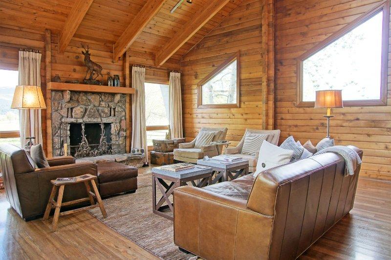 Una exquisita sala de estar con chimenea de leña y techos abovedados