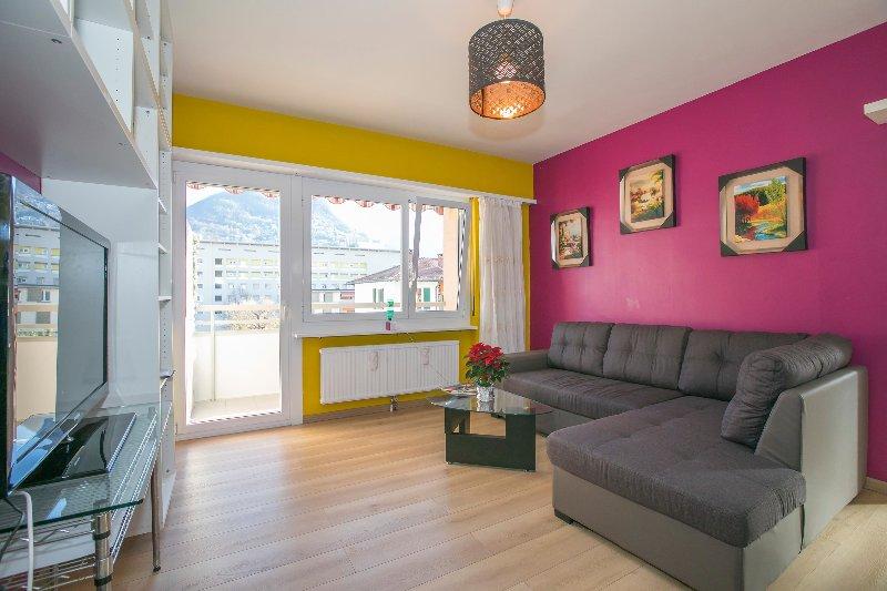Kleurrijke woonkamer met slaapbank en toegang tot het balkon