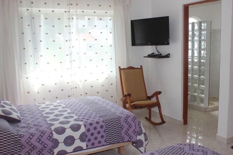 2 dormitorios con dos camas matrimoniales, baño privado, TV y vistas a la piscina