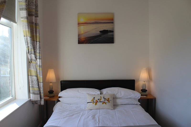 Light airy double bedroom with bedside tables and lights.