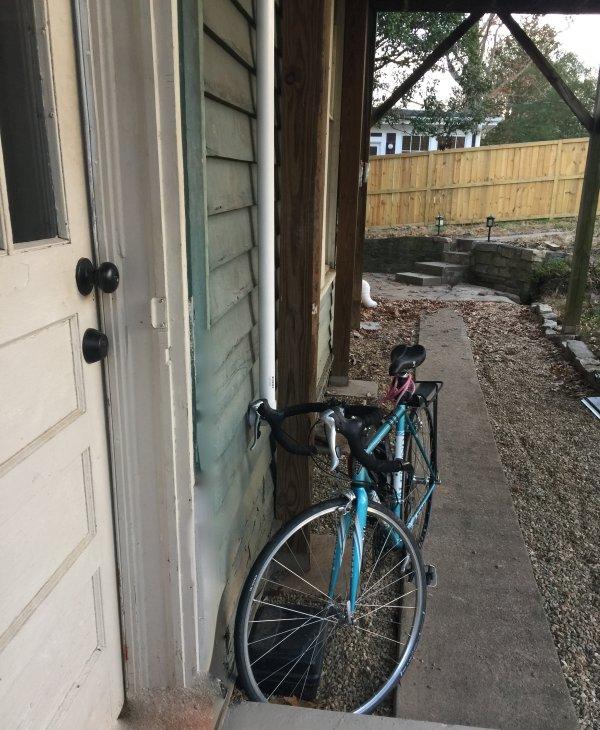 Un camino de cemento conduce desde la zona de porche en torno a la puerta trasera que conduce a la cocina.