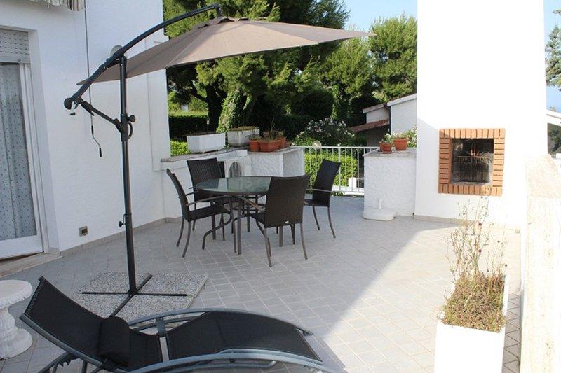 terraza con muebles de jardín, barbacoa y vistas al mar