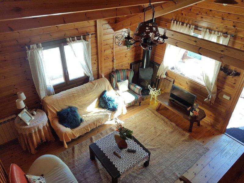 Vista del salón con amplios ventanales al bosque.