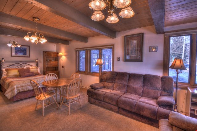 The living area features a fireplace, comfortable sofas and seating, as well as a dining area.