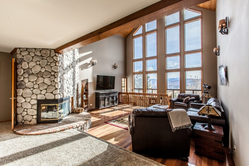 Living room with vaulted ceilings and wood burning fireplace surrounded by river rock