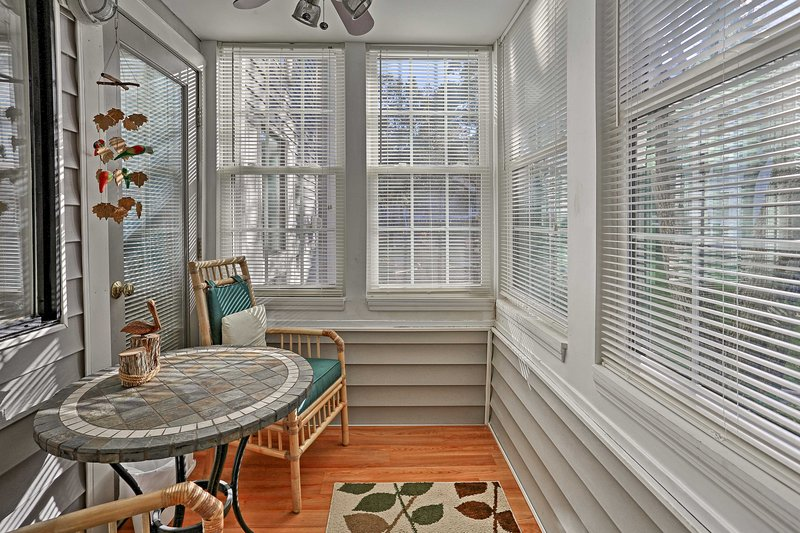 Sip your morning coffee in this quaint screened-in porch.