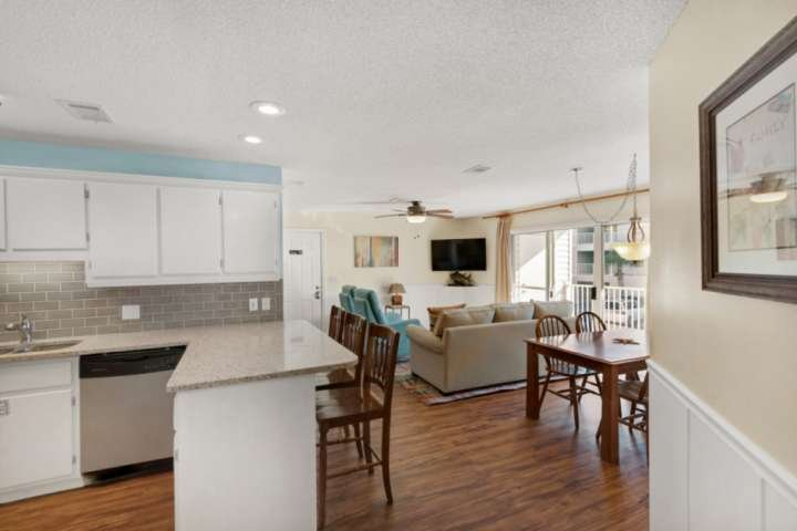 Open living area features kitchen and dining area with access to balcony.