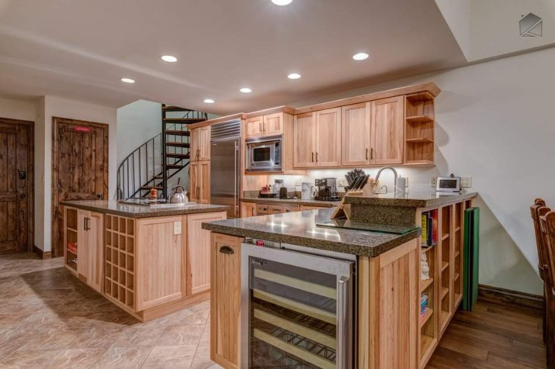 A wine fridge and rack are built into the light-stained wood furnishings in the kitchen.