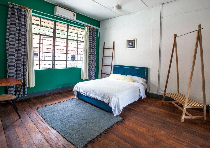 Master Biedroom mit A / C und Deckenventilator, Queen-Size-Bett, Schreibtisch und Kleiderbügel.