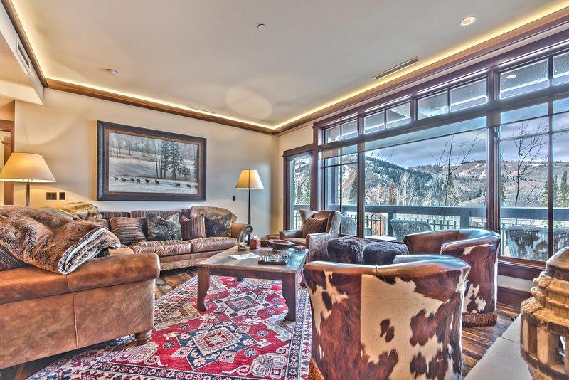 Salon spacieux avec mobilier de montagne confortable, cheminée, terrasse privée et vue imprenable!