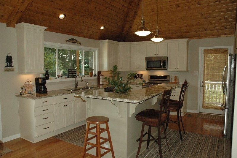 Upgraded kitchen with granite and stainless appliances.