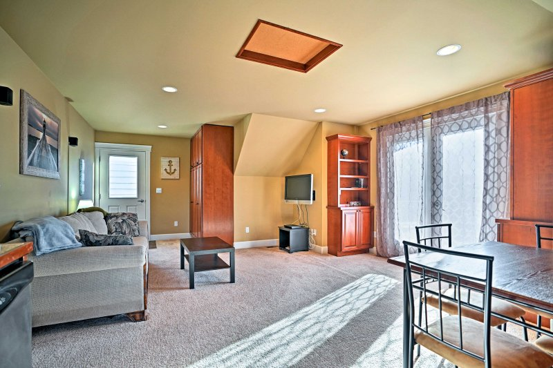 The clean, modern apartment features an open floor plan combining the living room, dining area and kitchen.
