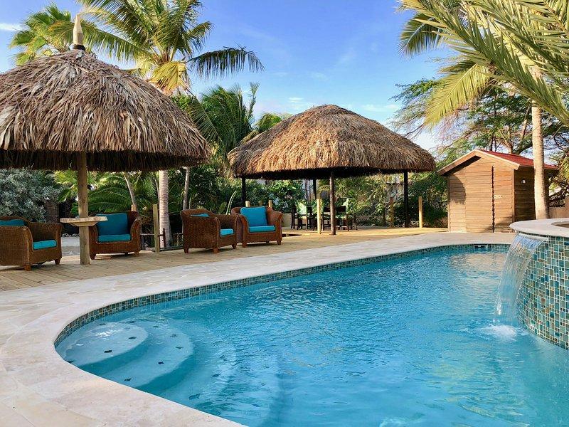 jardines tropicales y cabañas de estilo de Bali que rodean la gran piscina