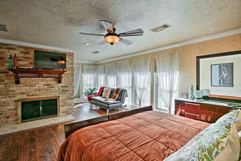 Luxury flourishes through the master bedroom boasting a gas fireplace and flat-screen cable TV.