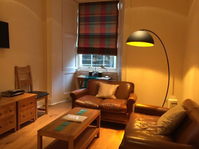 Livingroom beautifully furnished with leather sofas and oak furniture.