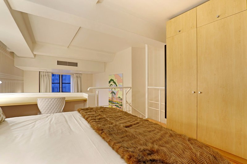 Art Deco Loft bedroom with  a desk area and spacious cupboards