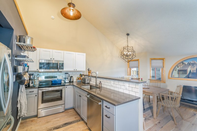 The kitchen is a chef's delight with professional grade cookware and small appliances including a blender, mixer, waffle iron, tea kettle, coffee maker, burr grinder, and French press.
