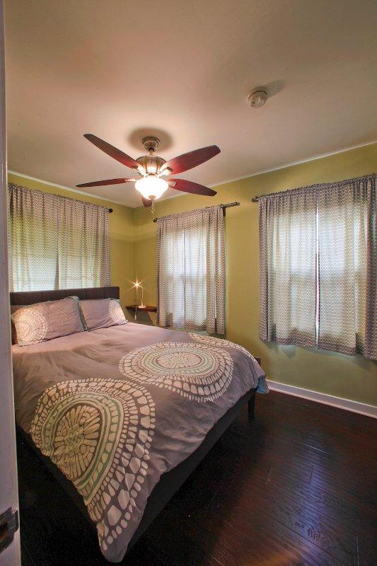 Quarto com cama queen size, ventilador de teto e armário com cômoda.