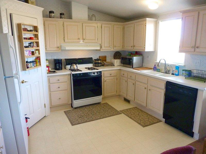 Cucina completa con frigorifero, congelatore, piano cottura, forno, microonde, lavastoviglie, tostapane, dispensa