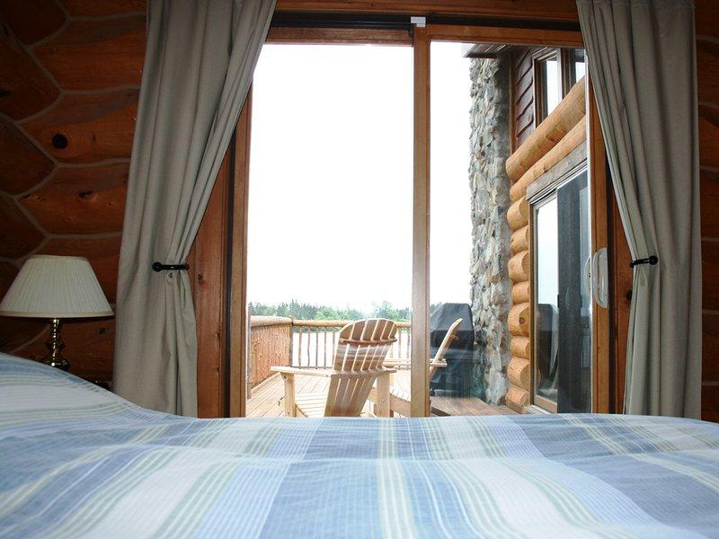 Habitación en Castaway Ocean Lodge ofrece cama y puertas de patio de tamaño queen que conducen a la cubierta