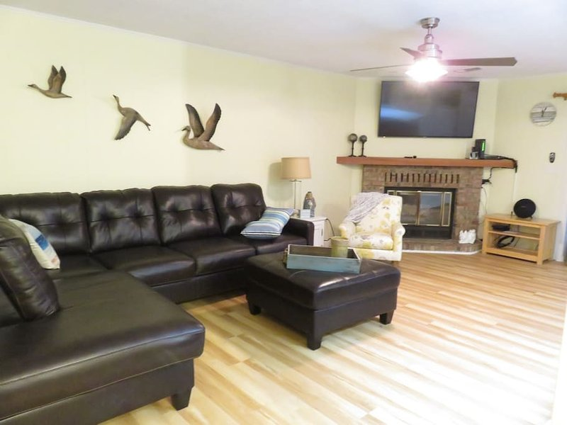 Living room has a 60 inch 4K TV. Cozy fireplace and new living room sectional.