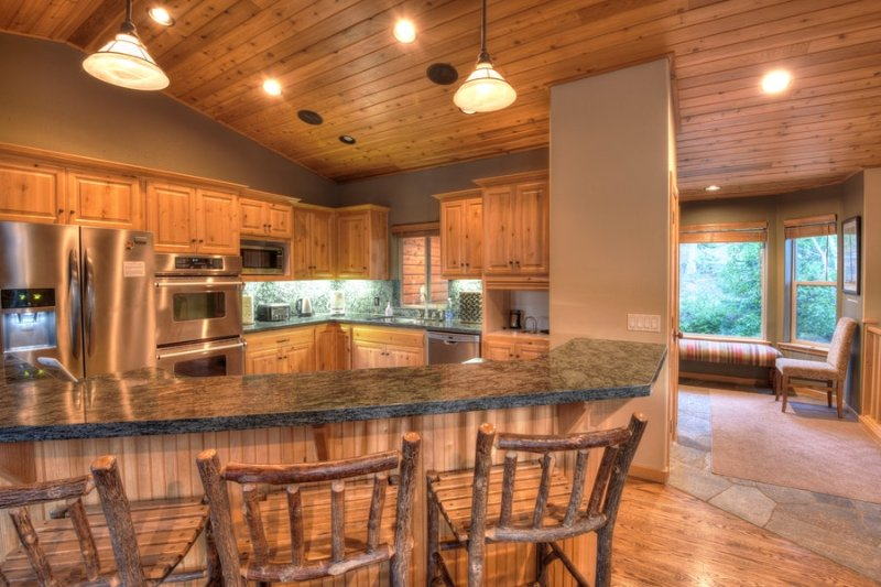Granite countertops, kitchen stainless steel amenities, and a breakfast bar