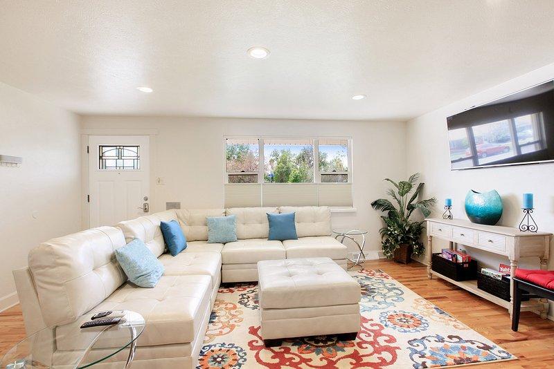 Sala principal de piso con 55 pulgadas de TV inteligente, sofá seccional, tablero y juegos de cartas