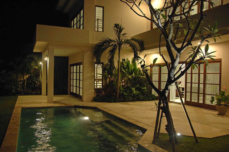 Villa from pool with balcony suite in distance at night