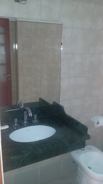 sink with marble countertops and large mirror