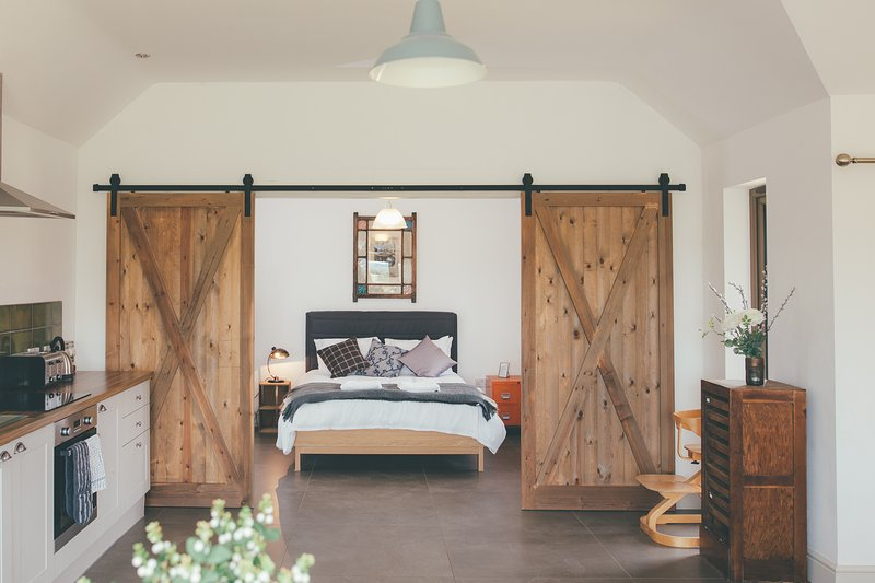 Bespoke barn doors frame the master bedroom in Alice Barn