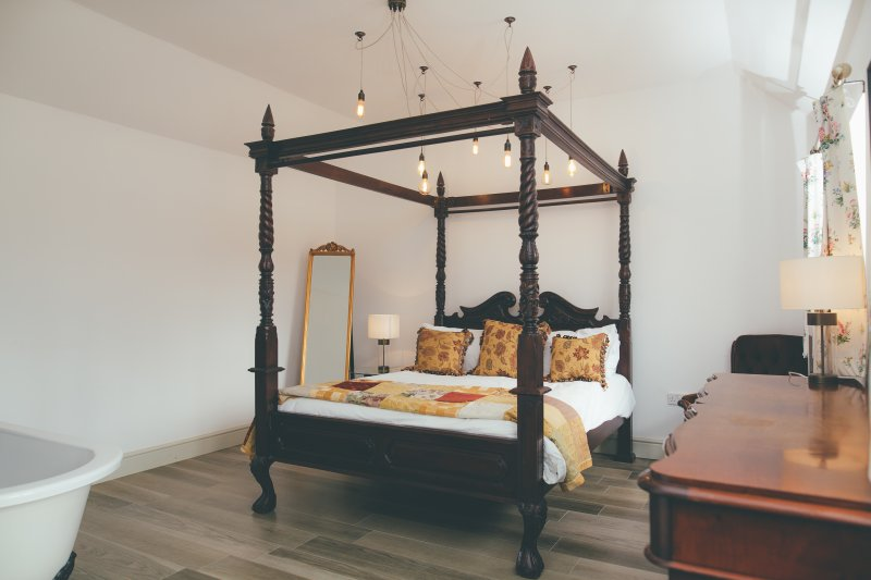 The master bedroom in Amba Barn with four poster bed and freestanding bath