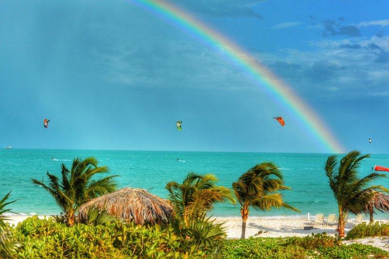 La playa y kiteboarder en la distancia bajo un arco iris fabuloso