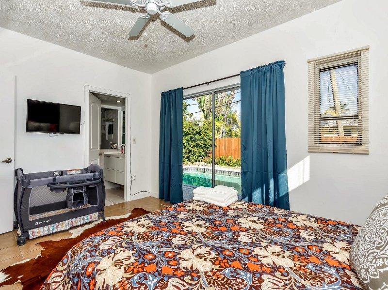 First bedroom features a comfortable queen bed, dresser, chic bear rug & has en-suite full bathroom