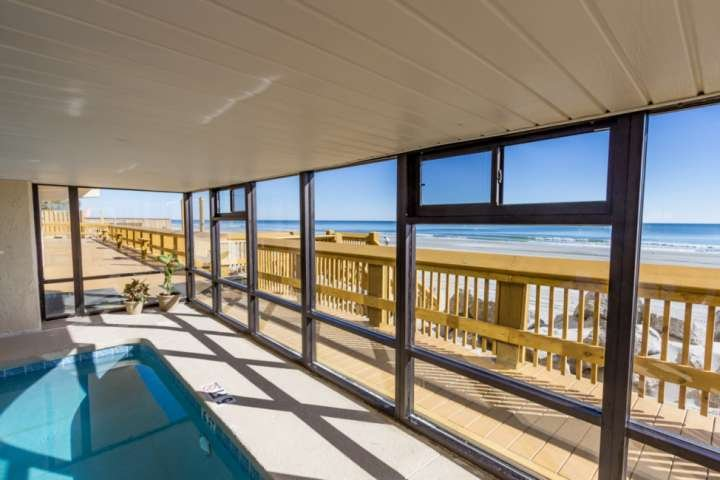 Large wooden sundeck and stairway to the beach, from the indoor pool area.