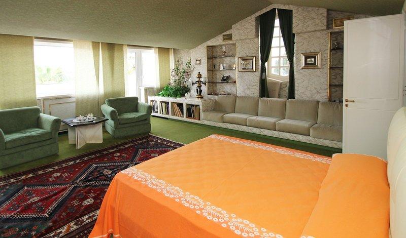 dormitorio de oliva con cómodos sillones y balcón privado
