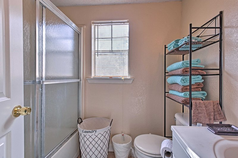 The bathroom features a shower/tub combo and vanity sink.