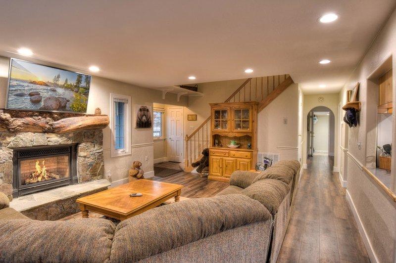 sala de estar con chimenea de piedra y TV de pantalla plana