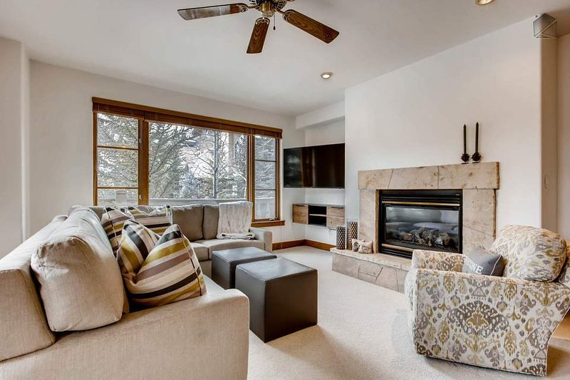 There is ample seating in the main living area, surrounding a gas fireplace and wall-mounted TV.