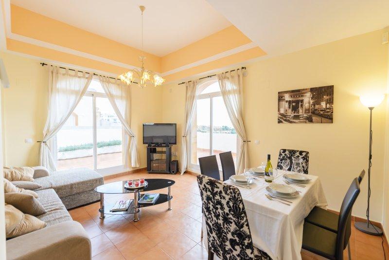 Mooie, lichte woonkamer met openslaande deuren naar wrap around terras.
