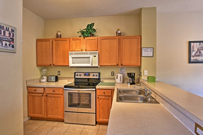 The full kitchen is equipped with stainless steel appliances and ample counter space.