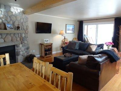 De woonkamer is voorzien van lederen meubels, een flatscreen-tv en een open haard